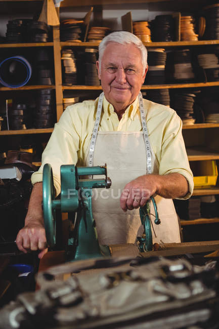 Portrait of shoemaker standing with sewing machine in workshop — Stock Photo