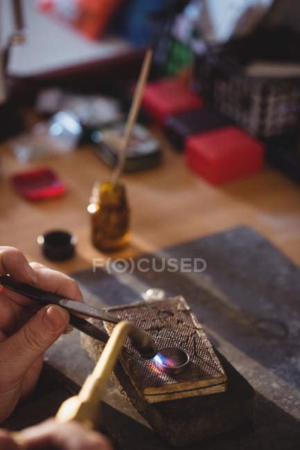 Cropped image of Goldsmith crafting ring by burner in workshop — Stock Photo