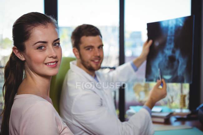 Terapeuta masculino que muestra radiografía a paciente femenino en clínica - foto de stock
