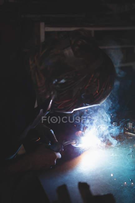 Blacksmith welding a metal in workshop — Stock Photo