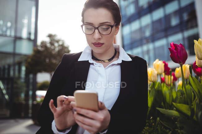 Giovane donna d'affari utilizzando il telefono cellulare da fiori — Foto stock