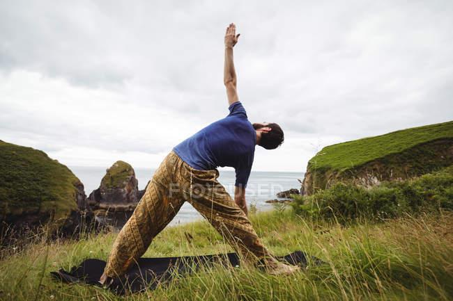 Задний вид человека, выполняющего упражнения на растяжку на скале — стоковое фото