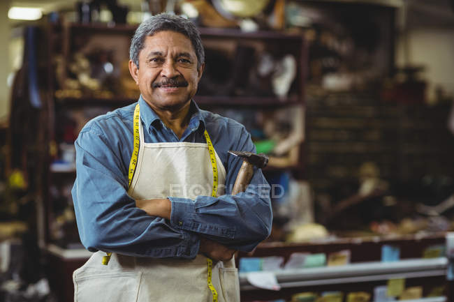 Confident shoemaker standing with arms crossed in workshop — Stock Photo