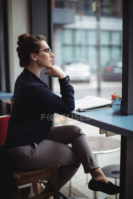 Businesswoman sitting by table in cafe — Stock Photo