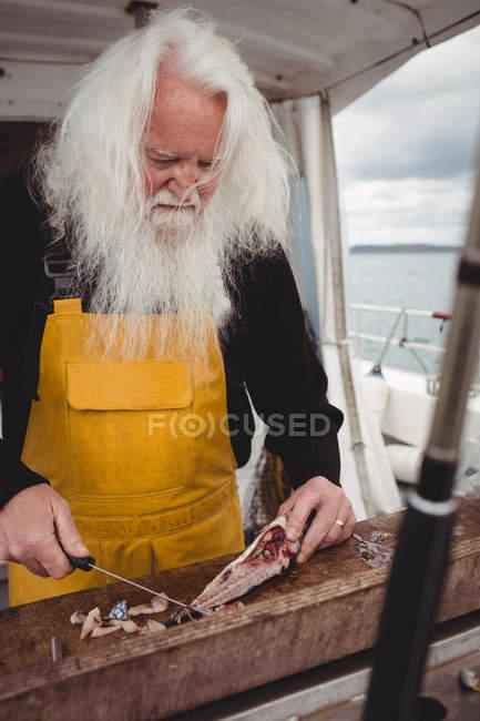 Nahaufnahme eines Fischers beim Filetieren von Fischen im Boot — Stockfoto