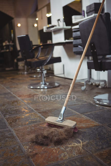 Hair waste and broom on floor in salon — Stock Photo