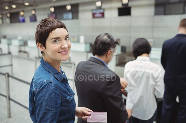 Жінка дивиться в камеру під час очікування в черзі на реєстрації разом із авіаквитком з багажем всередині терміналу аеропорту пасажирами — стокове фото