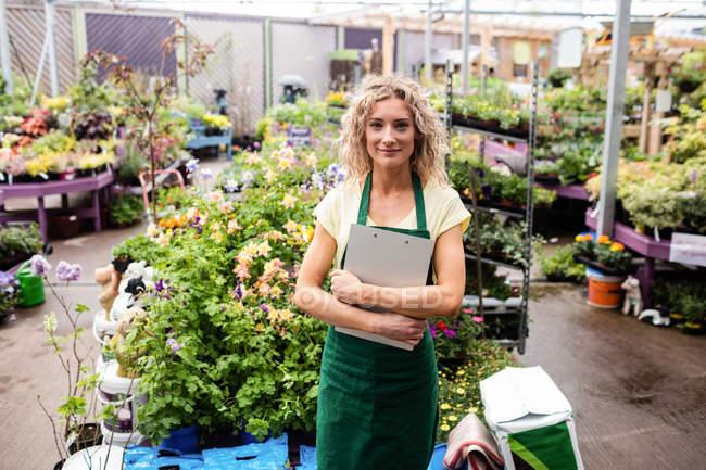 Portrait of female florist standing in garden centre — Stock Photo