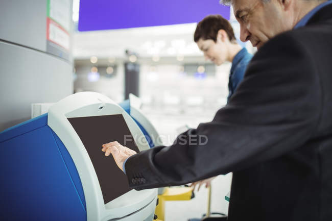 Businessman using self service check-in machine at airport — Stock Photo