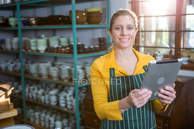 Portrait of female potter using digital tablet in pottery workshop — Stock Photo