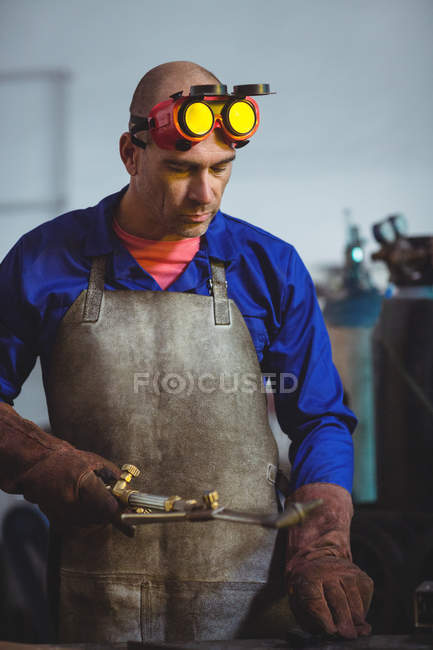 Чоловічий зварювальник, тримаючи факел зварювання в майстерні — стокове фото