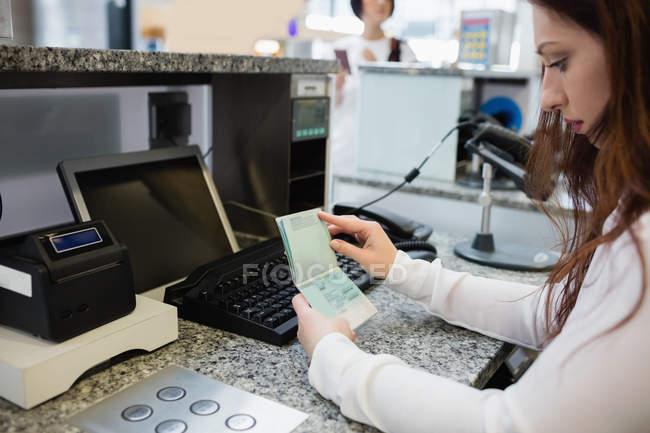 Línea aérea llegadas asistente control de pasaporte del pasajero en el mostrador de facturación de aeropuerto - foto de stock
