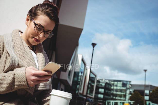 Giovane donna che utilizza il telefono cellulare contro edificio — Foto stock