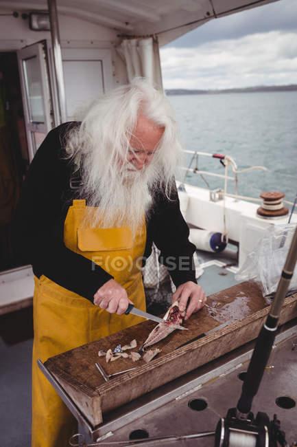 Nahaufnahme eines Fischers beim Filetieren von Fischen auf einem Boot — Stockfoto