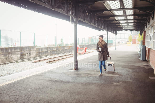 Full length of woman carrying baggage while walking at railroad station platform — Stock Photo
