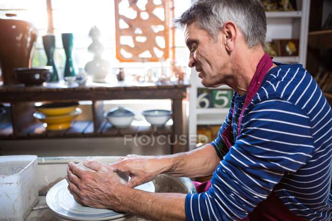 Oleiro masculino fazendo pote na oficina de cerâmica — Fotografia de Stock