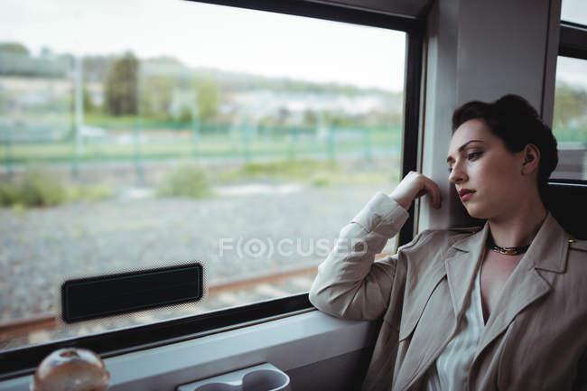 Cansado mulher sentada pela janela do trem — Fotografia de Stock
