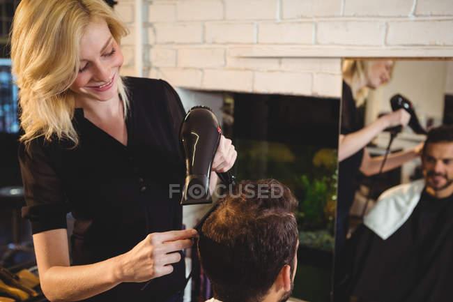 Homme souriant se faire sécher les cheveux avec sèche-cheveux dans le salon — Photo de stock