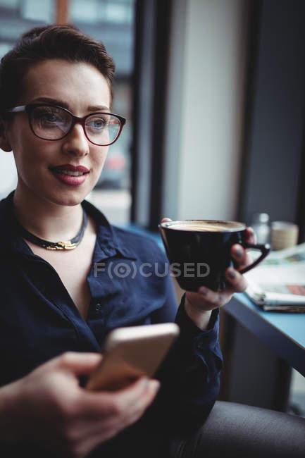 Junge Geschäftsfrau hält Handy in Café — Stockfoto