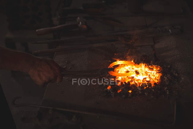 Close-up of blacksmith heating metal horseshoe in the forge on coals — Stock Photo