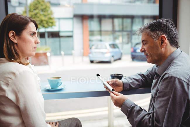 Homme utilisant un téléphone portable tout en parlant avec une femme à la cafétéria — Photo de stock