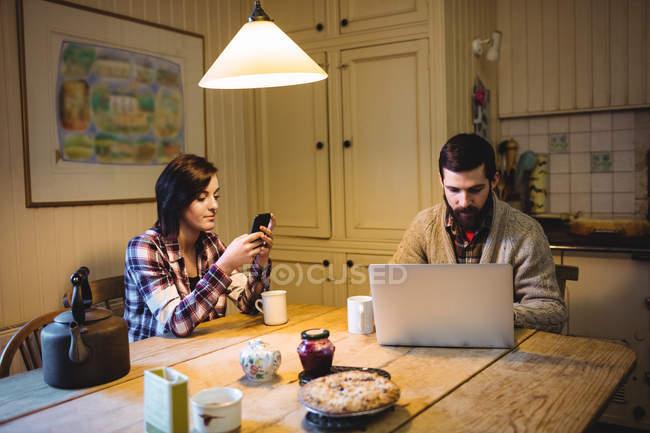 Casal usando laptop e telefone celular em casa — Fotografia de Stock