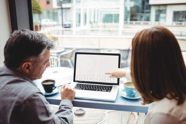 Mann und Frau schauen in Cafeteria auf Laptop — Stockfoto