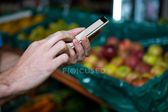Cropped image of Man using smartphone while shopping in supermarket — Stock Photo