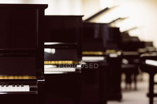 Vintage-Klaviere im Werkstattinnenraum arrangiert — Stockfoto