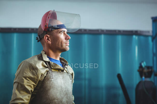 Side view of Male welder standing and looking away in workshop — Stock Photo