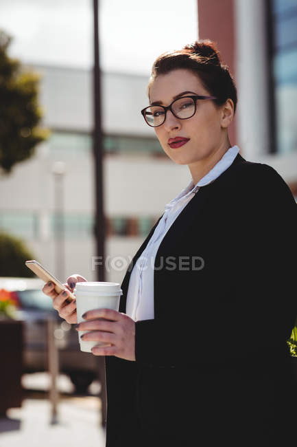 Portrait of young businesswoman holding mobile phone and disposable coffee cup — Stock Photo