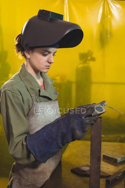 Seitenansicht Schweißerin begutachtet Metallstück in Werkstatt — Stockfoto