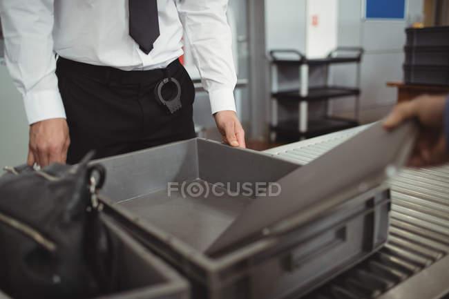 Homem colocando portátil em bandeja para verificação de segurança de aeroporto em aeroporto — Fotografia de Stock