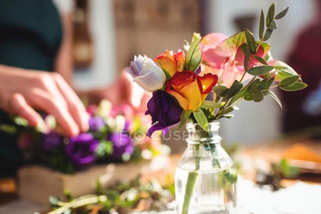 Закри квітів у пляшці при жіночий флорист підготовку квітковий букет у фоновому режимі — стокове фото
