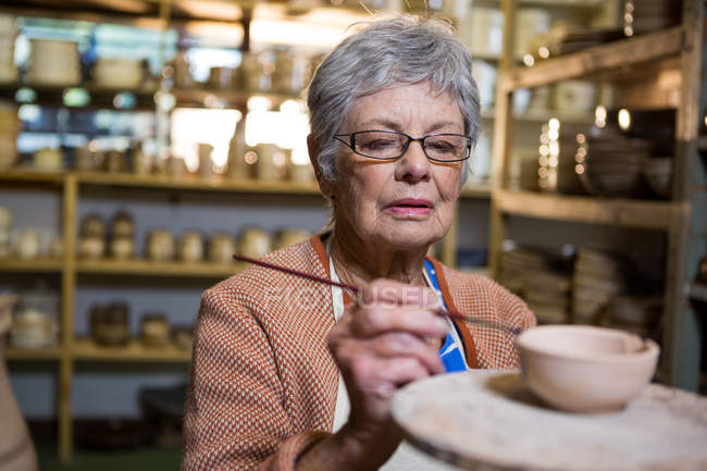 Female potter painting on bowl in pottery workshop — Stock Photo