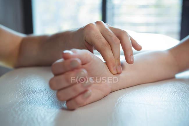 Imagen recortada del terapeuta revisando el pulso del paciente en la clínica - foto de stock