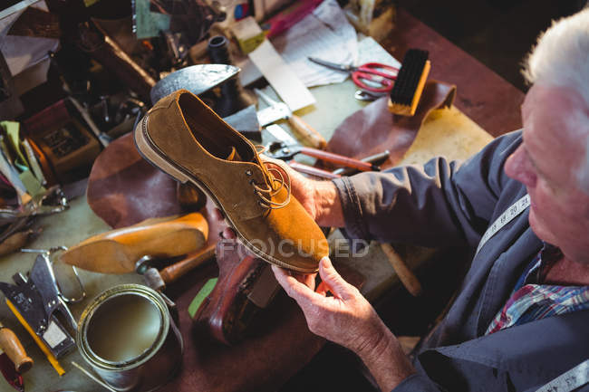 Shoemaker examining a shoe in workshop — Stock Photo