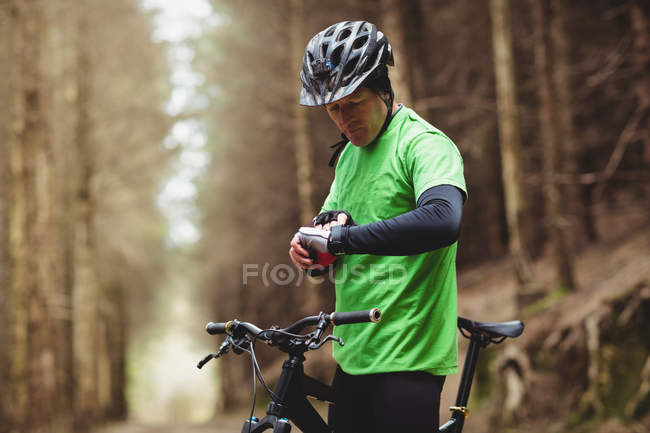 Side view of mountain biker checking time while riding in forest — Stock Photo