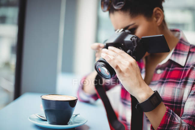 Woman photographing coffee cup while standing at restaurant — Stock Photo