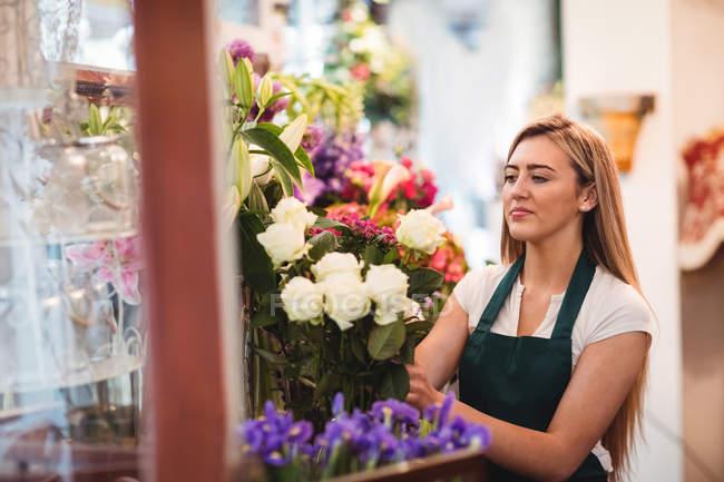Floristería femenina arreglando flores en la floristería - foto de stock