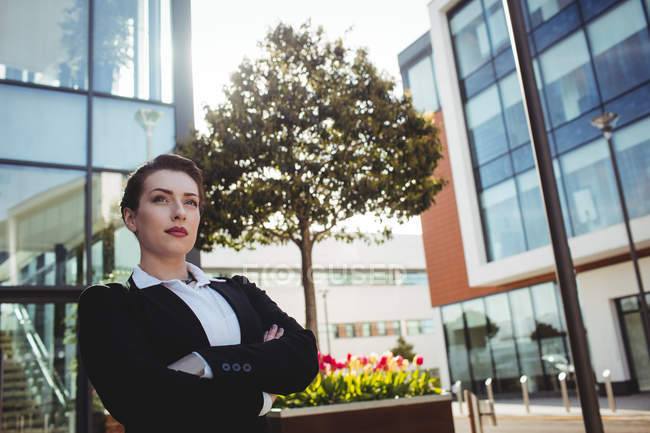 Confident businesswoman with arms crossed standing by building — Stock Photo