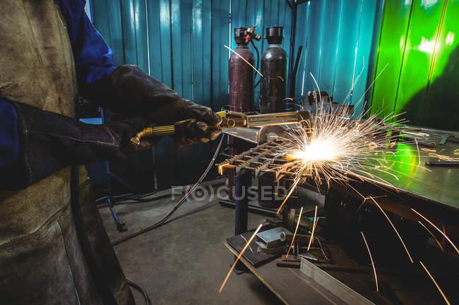 Средняя часть женского сварщика работает на куске металла в мастерской — стоковое фото