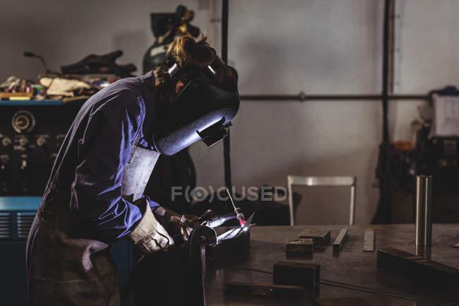 Вид збоку жіночий зварювальника, працюючи на шматок металу в майстерні — стокове фото