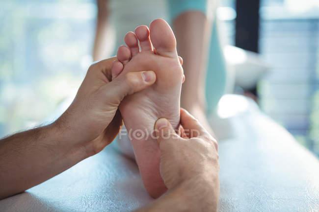 Imagen recortada de fisioterapeuta masculino dando masaje en los pies al paciente femenino en clínica - foto de stock