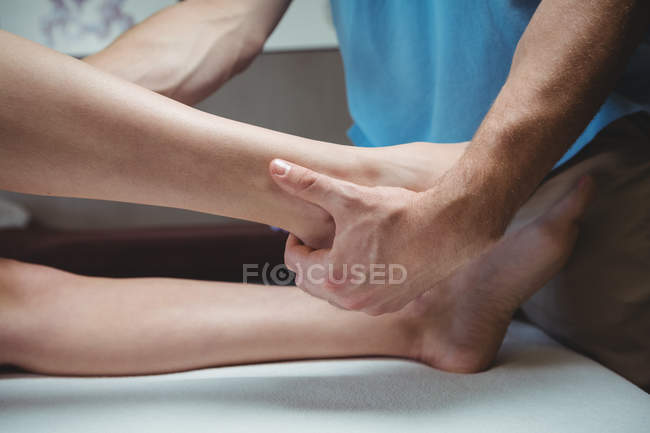 Cropped image of Physiotherapist giving physical therapy to leg of female patient in clinic — Stock Photo