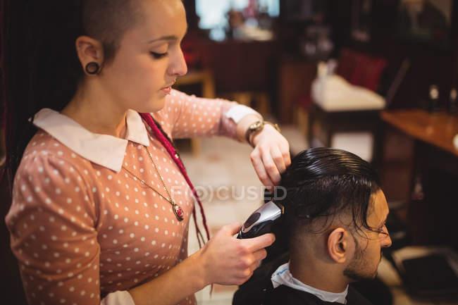 Homem recebendo seu cabelo aparado com aparador na barbearia — Fotografia de Stock