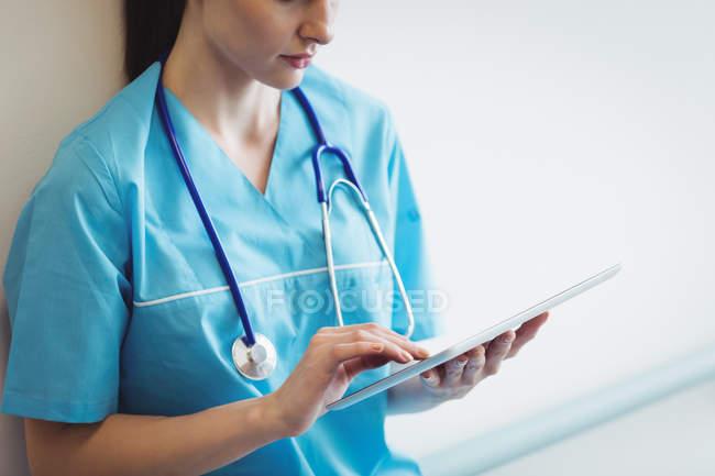 Медсестра с помощью цифрового планшета на стене больницы — стоковое фото