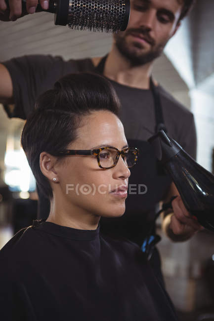 Woman getting her hair dried with hair dryer in hair salon — Stock Photo