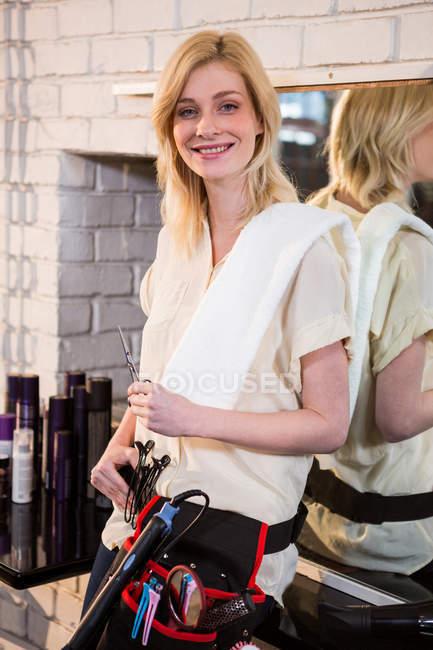 Ritratto di parrucchiera sorridente che tiene le forbici in salone — Foto stock