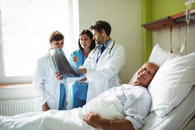 Médicos interactuando sobre informe de la radiografía con el paciente con el paciente en el hospital - foto de stock